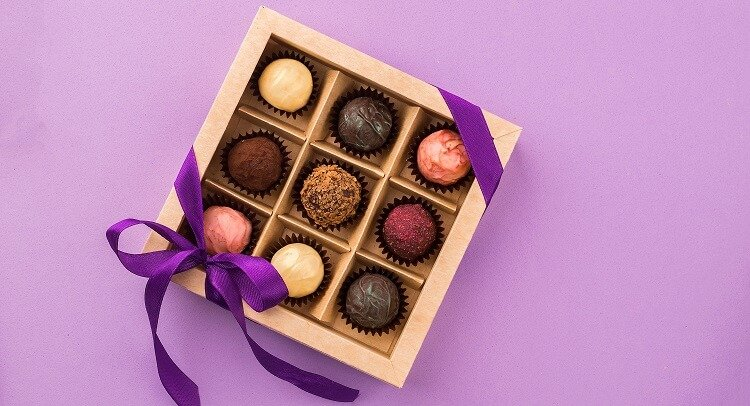 Chocolate Truffles in gift box with purple background