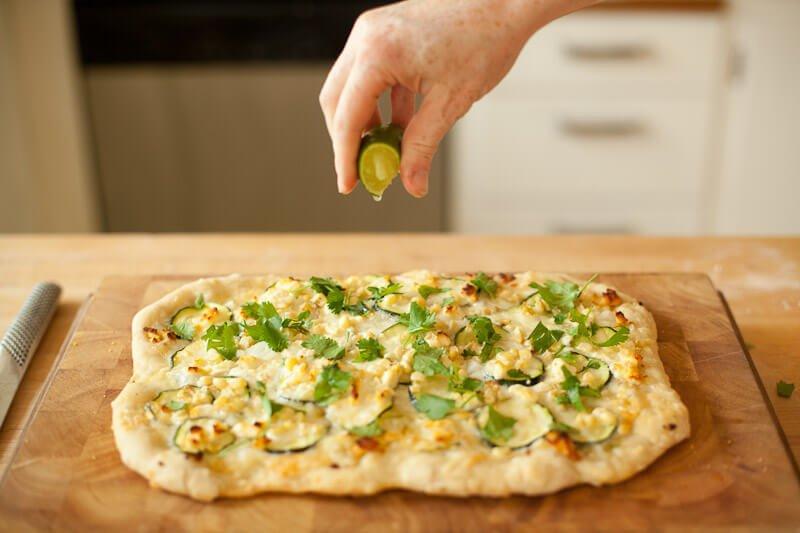 chef dropping lemon juice on Corn and Zucchini Pizza