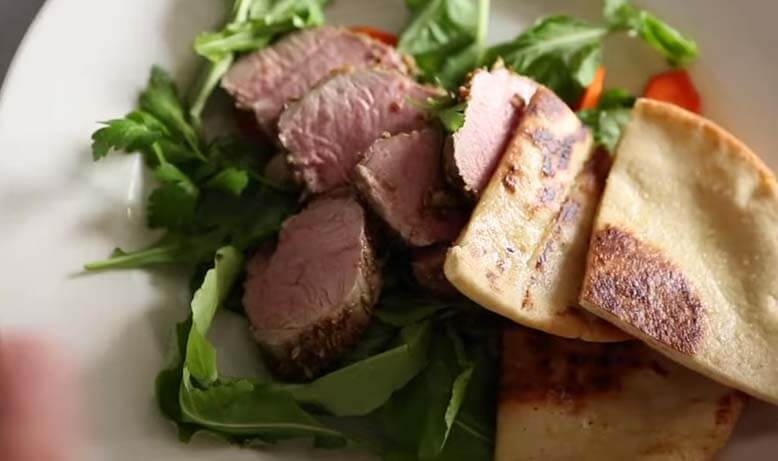 Fennel Crusted Pork Tenderloin Serving in white plate on wood table